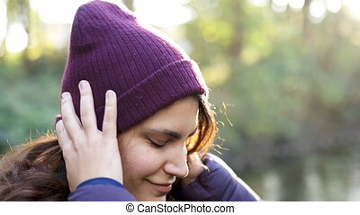 Close-up of beautiful brunette woman wearing knitted hat smiling next to river in the forest. Happy woman in forest with river as background. Adventurous day in nature