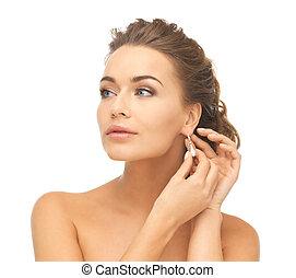 woman wearing shiny diamond earrings - close-up of beautiful...