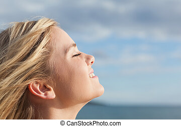 Close up of beautiful woman with eyes closed against sky