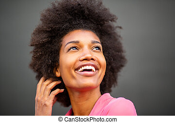 Close up of beautiful young african american woman laughing with hand in hair against gray wall