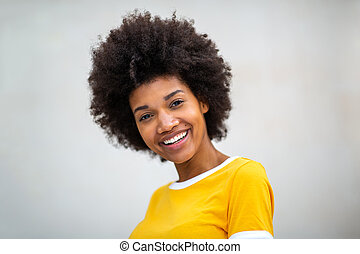Close up of beautiful young black woman smiling by white background