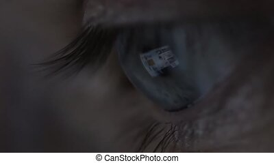 Close-up of beautiful young man eyes looking at monitor, working with computer, laptop. Monitor light is reflected in brown eyes. Evening busy freelancer working in night.