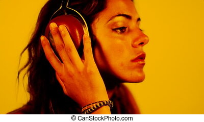 close-up of beautiful young woman listening to music on headphones