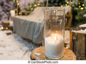 Close up of big candles in glass vases in a snow-covered park or a forest while snowing