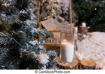 Close up of big candles in glass vases near fir-tree in a snow-covered park