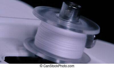 Close up of big spool with thin white thread on working professional sewing machine. Shot of sewing bobbin being wound up on sewing machine.