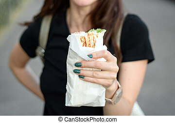 Close-up of bitten Shawarma in a woman's hand