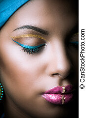 close up of black African woman face with golden and blue makeup