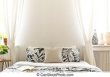 Close-up of black and white flower design pillows on a bed. Lace curtains on the sides of a headboard in a bright bedroom interior. Copy space background wall. Real photo.