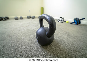 Close up of black kettlebell inside a fitness room with gray carpet on the floor