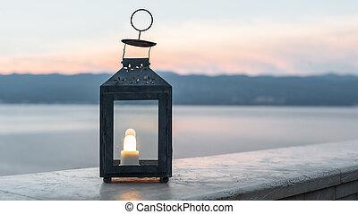 Close up of black lantern shines at sunset