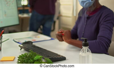 Close up of black woman using hand sanitizer while working in office room in new normal company workplace. African employee cleaning disinfecting hands using alcohol gel against corona virus.