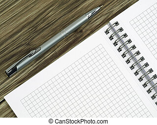 close up of blank notebook and a pen on wooden office desk with copy space