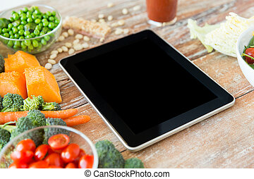 close up of blank tablet pc screen and vegetables
