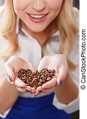Close up of blond woman holding coffee beans