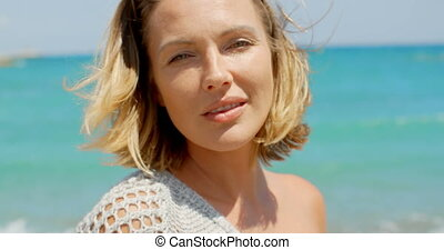 Close Up of Blond Woman in front of Blue Ocean