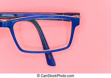 Close up of Blue glasses on pink background, top view.