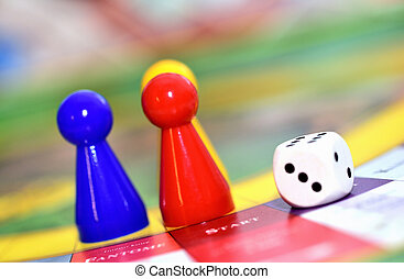 Close-up of blue, red, yellow play figures and dice on the board game.
