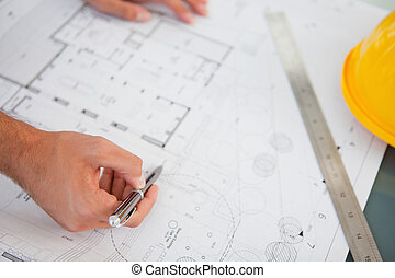 Close up of blueprints with a person making adjustments