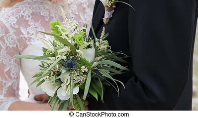 close-up of bohho wedding bouquet in hands of bride and groom