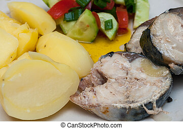 boiled potatoes, vegetable salad and stewed mackerel on a plate