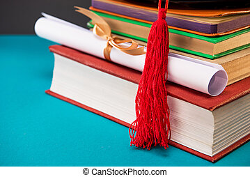 close up of books, diploma and graduation cap with tassel on blue, education concept