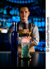 close-up of bottle and glass of cold blue alcoholic cocktail with ice on bar counter