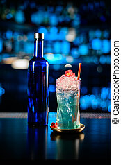 close-up of bottle and glass with cold blue alcoholic cocktail on bar counter