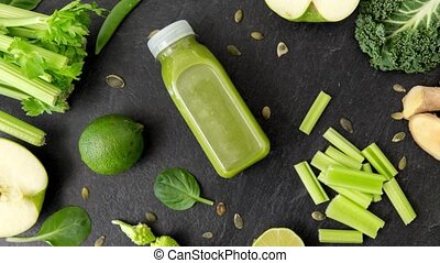 close up of bottle with green juice and vegetables - healthy...