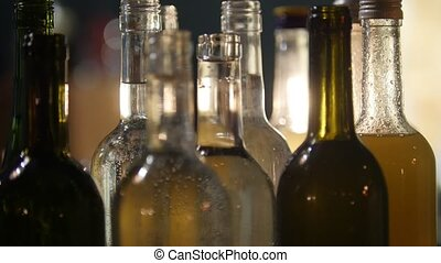 Close-up of bottles full of different alcohol at the bar with soft interior lighting