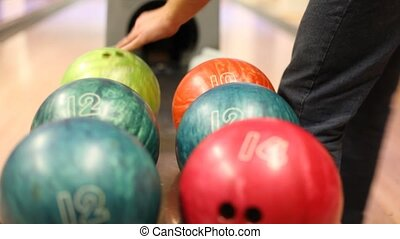 Close-up of bowling balls, man takes ball - Close-up of...