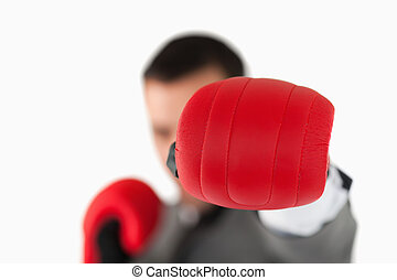 Close up of boxing glove being used to slam by businessman