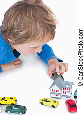 Close-up of boy playing with playhouse and toy cars over white background