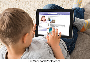 Boy Using Social Networking Site On Digital Tablet