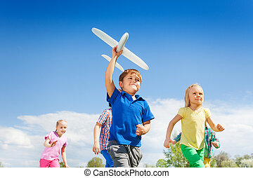 Close-up of boy with airplane toy and children