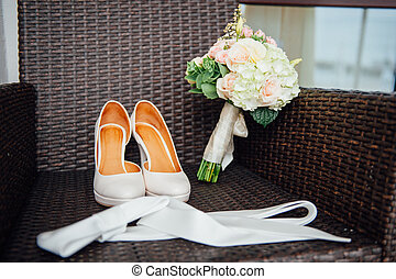 close-up of bridal bouquet of roses, wedding flowers for the ceremony on the bed in a hotel room with white shoes