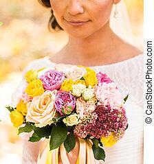 Close up of bride hands holding beautiful autumn wedding bouquet.