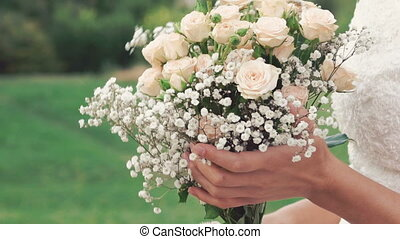 Close up of bride sniffing bouquet and smiling in the field. Slowly