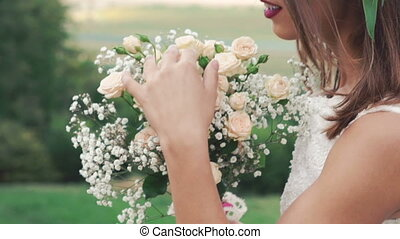 Close up of bride sniffing bouquet in the field. Slowly