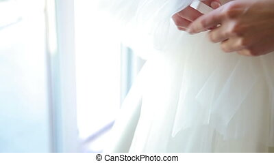 Close up of bride's hand holds veil