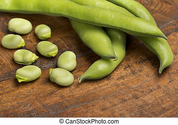 close up of broad beans on wooden background