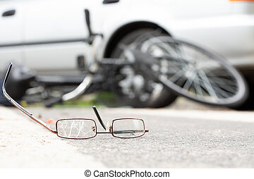 Close-up of broken glasses on a road with a blurred bike and car in the background