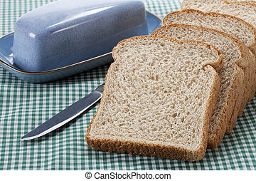 brown bread with knife on table cloth - Close-up of brown ...