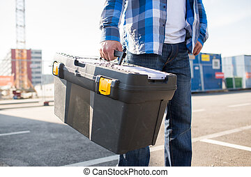 close up of builder carrying toolbox outdoors - building, ...