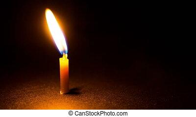 Close-up of burning candle on black background. Time lapse,...