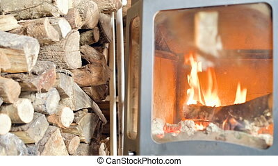 Close-up of burning firewood in a home-made modern stove behind refractory glass during the day next to a large pile of firewood. Eco-friendly energy