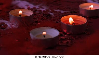 Close-up of burning tealight candle grouped together on red background. Romantic atmosphere with scented aroma tea light candles. Valentines background. Love