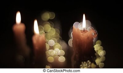 Close-up of burning wax candles burn out in the dark against various glare. Close-up view of candles in a dark room with a blinking bright spotlight. Scenery at night and warming bright background.