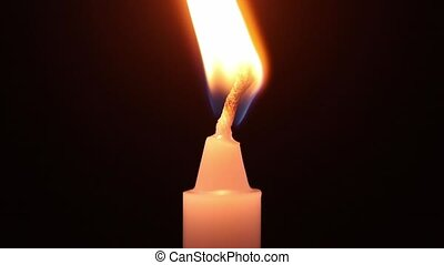 Close-up of burning white wax candle and blowing out on...