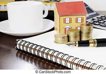 business fountain pen with coins stack and paper home on notepad for home repair loans concept
